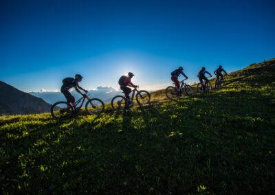 groupe de vététistes roulant sur une crête au coucher du soleil